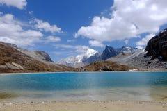Blå himmel med vit fördunklar över sjön och snöberget Arkivfoto