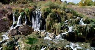 Blå himmel och gröna gräs omger lite vattenfallet i svandalen Idaho lager videofilmer