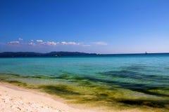 Blå himmel och kristallklart hav på en sandig strand med moln fotografering för bildbyråer