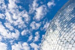 Blå himmel och moln som reflekterar på en byggnad med spegelförsett exponeringsglas Arkivbild