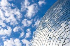 Blå himmel och moln som reflekterar på en byggnad med spegelförsett exponeringsglas Fotografering för Bildbyråer