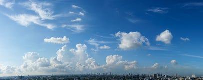 Blå himmel och vit fördunklar över cityscapen Royaltyfri Fotografi