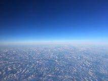Blå himmel och vita fluffiga moln som ses från nivån Royaltyfria Foton