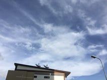 Blå himmel och vita moln över lyktstolpen och satellit- maträtt på taket fotografering för bildbyråer