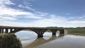 Blå himmel och vita moln, en liten bro över en liten flod royaltyfria bilder
