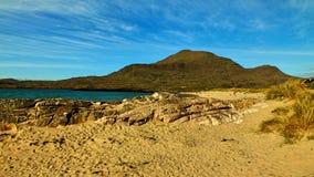 Blå himmel, sand och berg arkivbild
