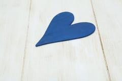 Blå hjärta på en vit bakgrund, trä målade grekblått royaltyfri bild