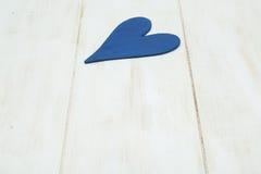 Blå hjärta på en vit bakgrund, trä målade grekblått royaltyfri fotografi