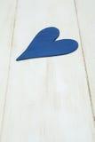 Blå hjärta på en vit bakgrund, trä målade grekblått royaltyfria bilder