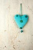 Blå hjärtahand - som göras på en träbakgrund Arkivbild