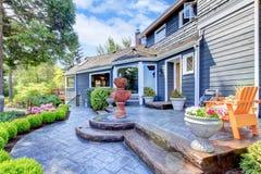 Blå husingång med springbrunnen och den trevliga uteplatsen. Arkivbilder