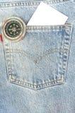 Blå jean med papper och kompasset i facket. Arkivfoton