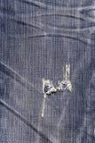 Blå jeantextur med ett hål och en tråduppvisning Royaltyfri Fotografi