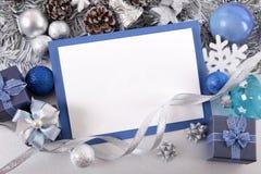 Blå julkortbakgrund med garneringar och kopieringsutrymme Royaltyfria Foton