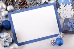 Blå julkortbakgrund med garneringar och kopieringsutrymme Arkivfoto