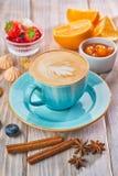 Blå kaffekopp med cappuccino, kanel och anis stekt ägg för kopp för frukostkaffebegrepp royaltyfri fotografi