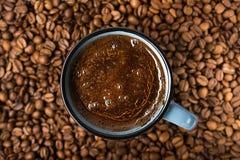 Blå kaffekopp med grillade bönor royaltyfri bild