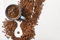 Blå kaffekopp med grillade bönor royaltyfria foton