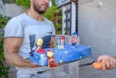 Blå kaka med diagram av superheroes för födelsedagen 1 royaltyfri fotografi