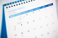 Blå kalender med fläcken på juli Arkivbild