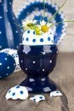 Blå keramisk ägghållare med blommor i äggshel, lycklig påsk! Arkivfoton