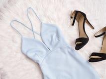 Blå klänning och svarta skor på vit päls, trendigt begrepp Royaltyfri Bild