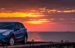Blå kompakt SUV bil med sporten och den moderna designen som parkeras på den konkreta vägen av havet på solnedgången milj?v?nlig  arkivbild