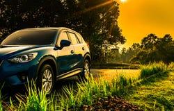 Blå kompakt SUV bil med sporten och den moderna designen som parkeras på den konkreta vägen på soluppgång med orange himmel Fotografering för Bildbyråer
