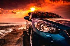 Blå kompakt SUV bil med sporten som är modern och den lyxiga designen som parkeras på den konkreta vägen av havet på solnedgången arkivbild