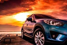 Blå kompakt SUV bil med sporten som är modern och den lyxiga designen som parkeras på den konkreta vägen av havet på solnedgången royaltyfria bilder