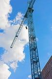 Blå konstruktionskran mot en molnig blå himmel Royaltyfri Fotografi