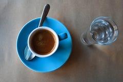 Bl? kopp av parfymerat espressokaffe med exponeringsglas av s?tvatten royaltyfria foton