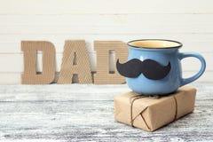 Blå kopp med en mustasch, gåvaasken och en inskriftfarsa i royaltyfria bilder