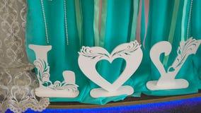 Blå kudde på den vita stolen och träordet FÖRÄLSKELSE Valentin eller bakgrund för bröllopdag man för begreppskyssförälskelse till stock video