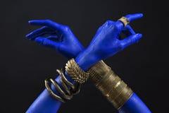 Blå kvinnas händer med indiska guld- smycken Orientaliska armband på en hand Guld- smycken och lyxig tillbehör på svart backgroun royaltyfri fotografi