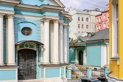 Blå kyrka med vita pelare i mitt av färgrika hus Arkivfoto