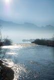 Blå lansdcape, reflekterande flod och berg med dimma i bet Arkivbild
