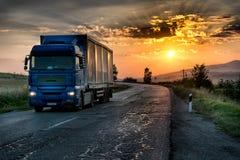Blå lastbil på den lantliga vägen för asfalt Royaltyfria Bilder
