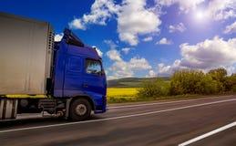 Blå lastbil på den lantliga vägen för asfalt Trafik på huvudvägen Royaltyfri Bild