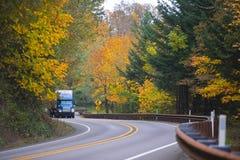 Blå lastbil på den spektakulära slingriga autemnhuvudvägen Royaltyfri Fotografi