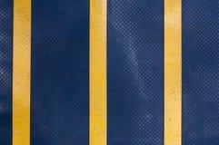 Blå lastbilpresenning med gula band Arkivbild