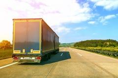 Blå lastlastbil på en tom motorväg Arkivfoton