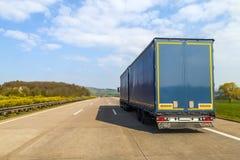 Blå lastlastbil på en tom motorväg Arkivfoto