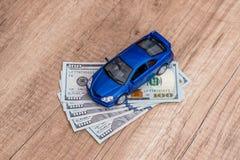 Blå leksakbil med oss dollar Royaltyfri Fotografi