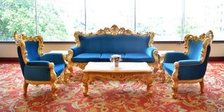 Blå lyxig soffa på en röd matta Royaltyfri Foto