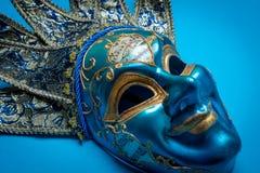 Blå Mardi Gras eller karnevalgyckelmakaremaskering på en blå bakgrund royaltyfria bilder