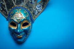 Blå Mardi Gras eller karnevalgyckelmakaremaskering på en blå bakgrund royaltyfri fotografi