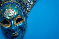 Blå Mardi Gras eller karnevalgyckelmakaremaskering på en blå bakgrund arkivfoton