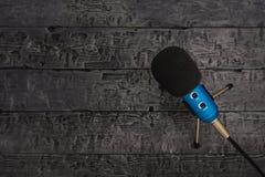 Blå mikrofon med svart tråd på den svarta trätabellen Utrustning för konferenser, musikstudior och möten arkivfoto