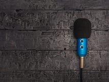Blå mikrofon med tråd på den svarta trätabellen Utrustning för konferenser, musikstudior och möten arkivfoton